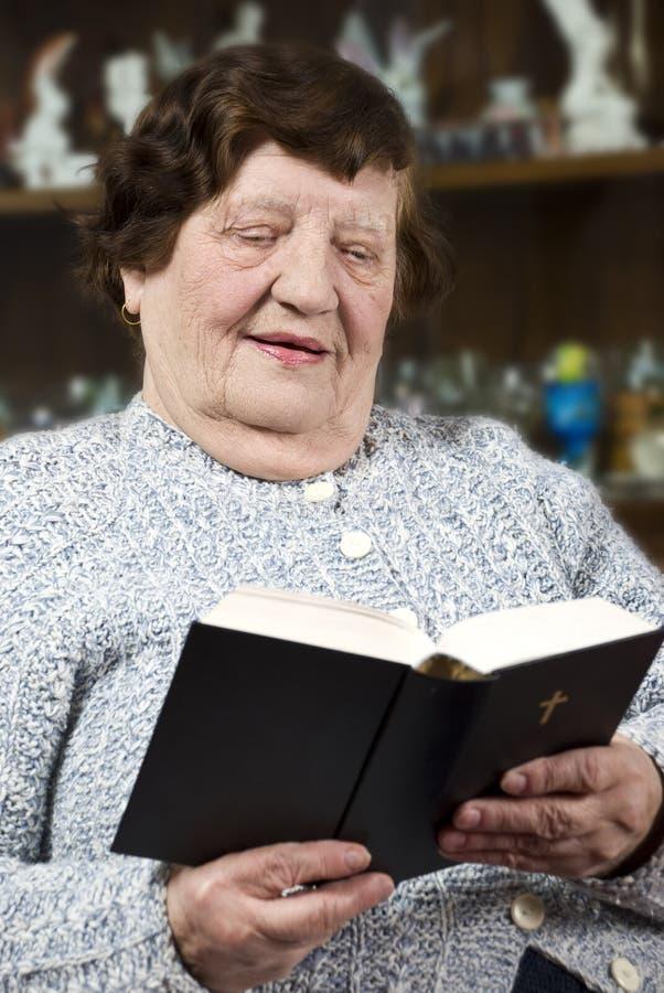 Elderly woman reading bible at home stock photos