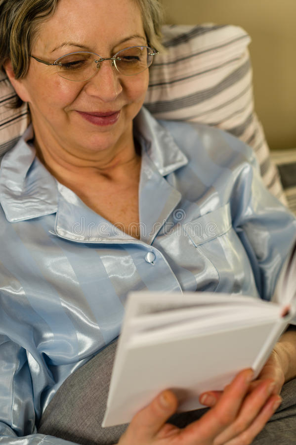 Elderly woman reading book lying in bed. Elderly smiling woman reading book lying in bed royalty free stock images
