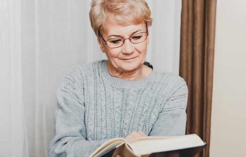 Elderly woman reading book stock image