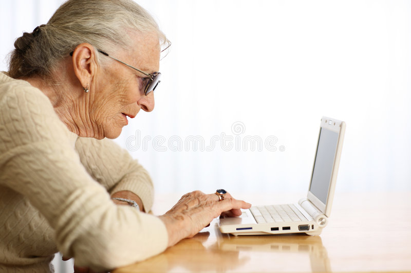 Elderly woman reading computer stock images