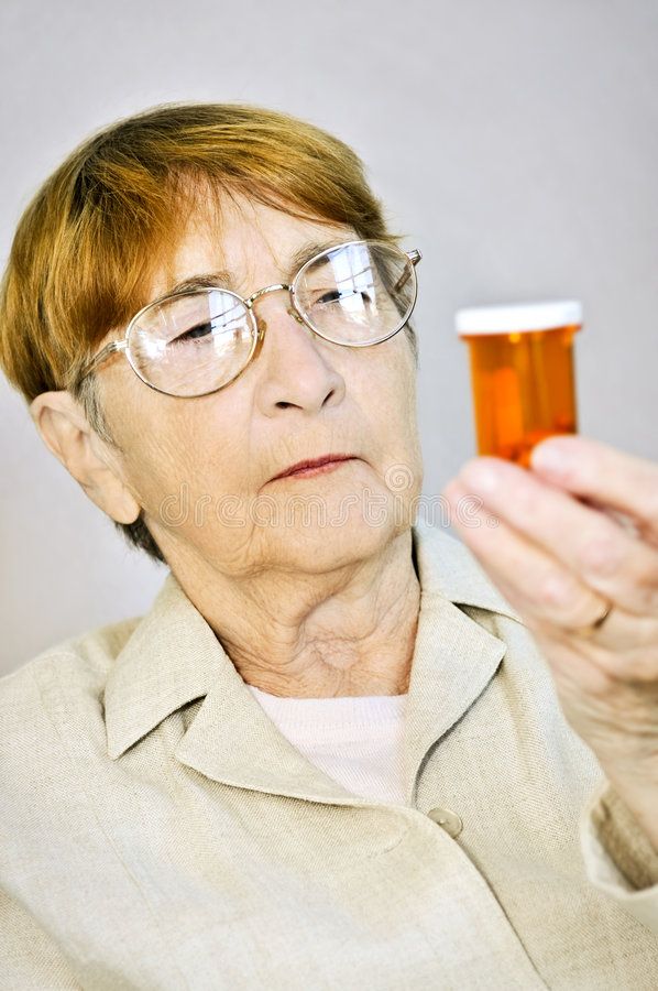 Elderly woman reading pill bottles royalty free stock photo