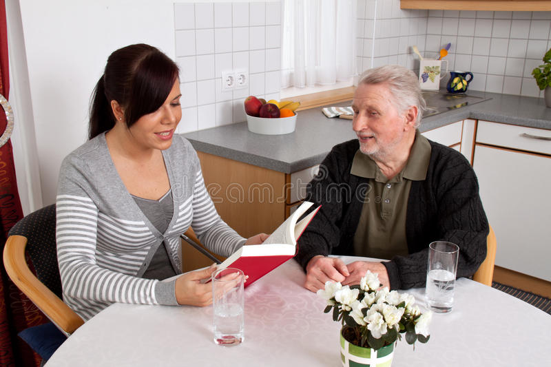 Elderly woman reads from a book. royalty free stock photography