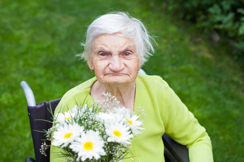 Elderly woman receiving flowers royalty free stock photo