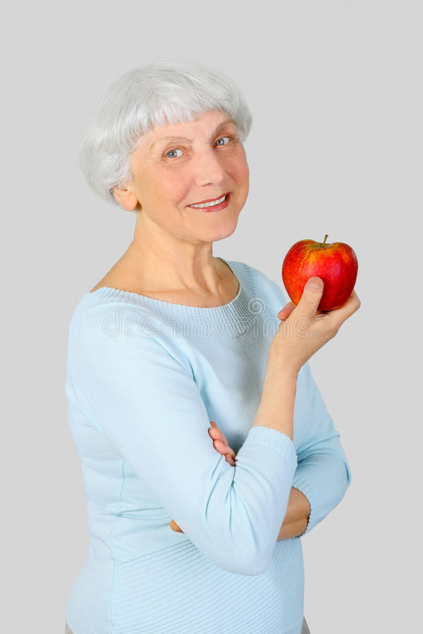 Elderly woman with red apple in hands on a light background stock photography