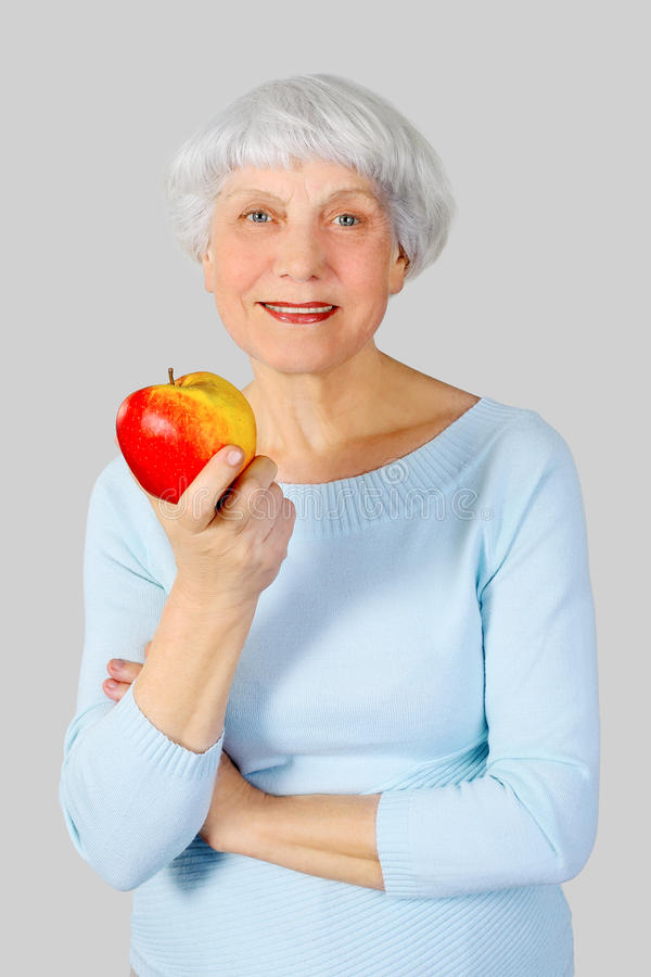 Elderly woman with red apple in hands on a light background in t stock photo
