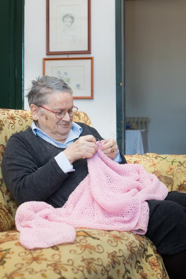 Elderly woman knitting pink wool portrait royalty free stock photo