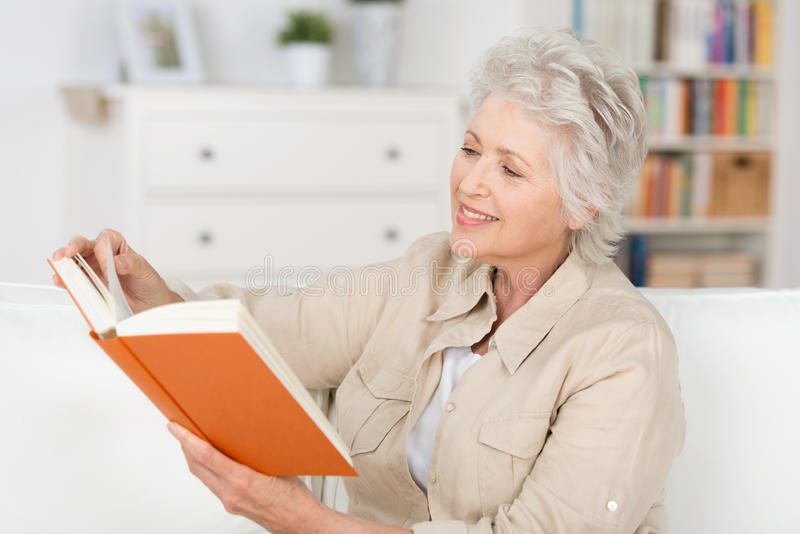 Elderly woman relaxing at home reading a book stock image