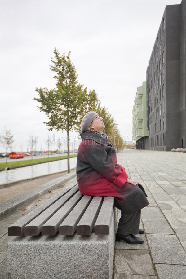 An elderly woman is resting on a bench, on the street and looking up royalty free stock photography
