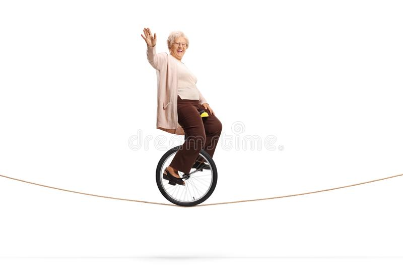 Elderly woman riding a unicycle on a rope and looking at the camera. Full length shot of an elderly woman riding a unicycle on a rope and looking at the camera stock images