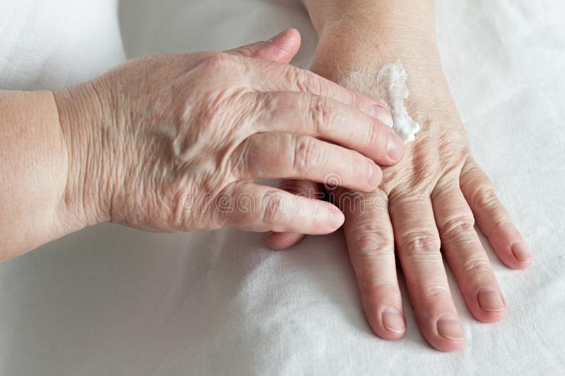 Elderly woman rubbing hand cream, white background, close-up, cosmetics stock photography