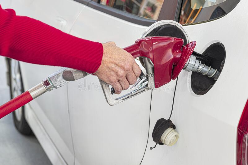 Elderly Woman's Hand Pumping Gasoline royalty free stock photos