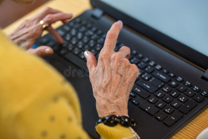 Elderly woman`s hands and laptop. stock photo