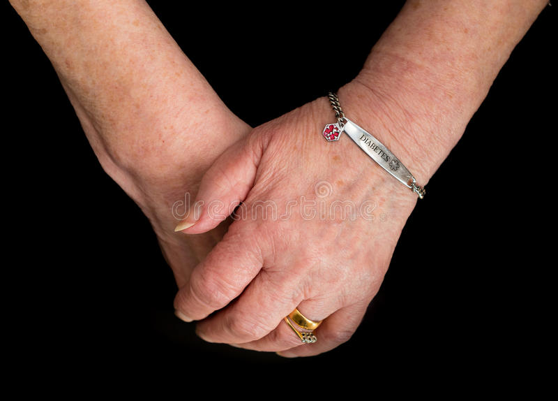 Elderly woman`s hands with medical alert bracelet for diabetes. stock photo