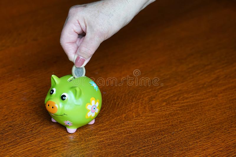 Elderly woman saves money. Close-up of senior woman hand putting coin into piggy bank. royalty free stock photography
