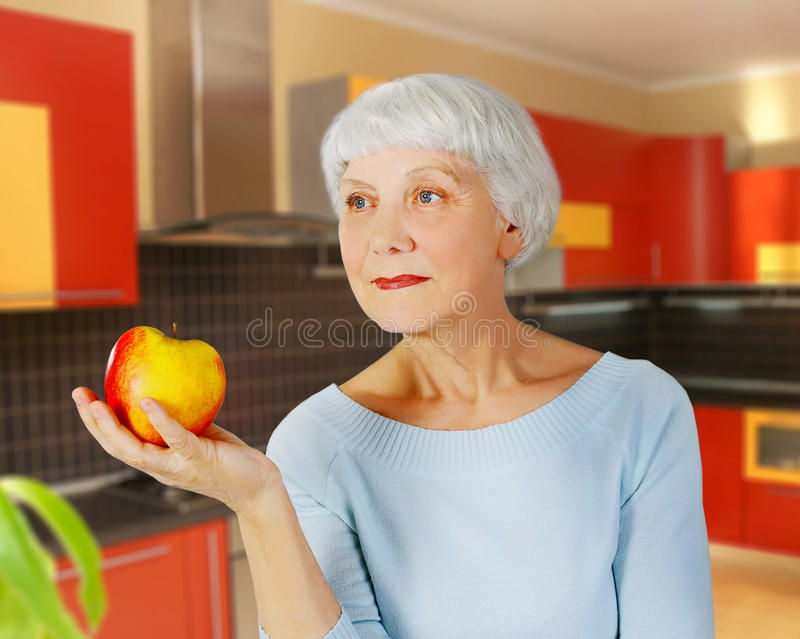 Elderly woman senior with red apple in his hand in the kitchen stock photos