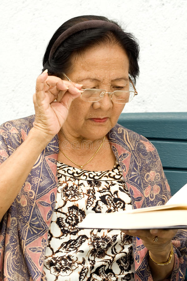 Elderly woman in serious reading royalty free stock image