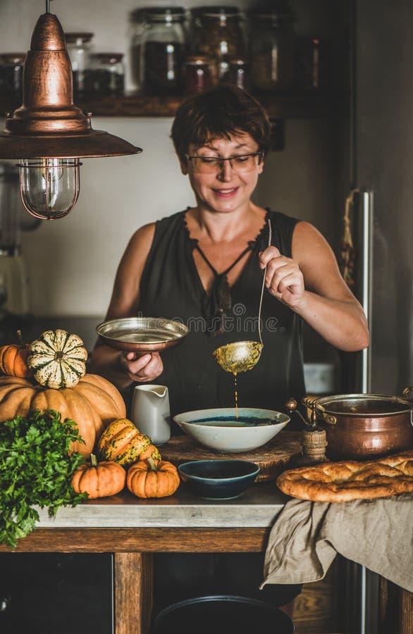 Elderly woman serving Autumn seasonal pumpkin cream soup royalty free stock photography