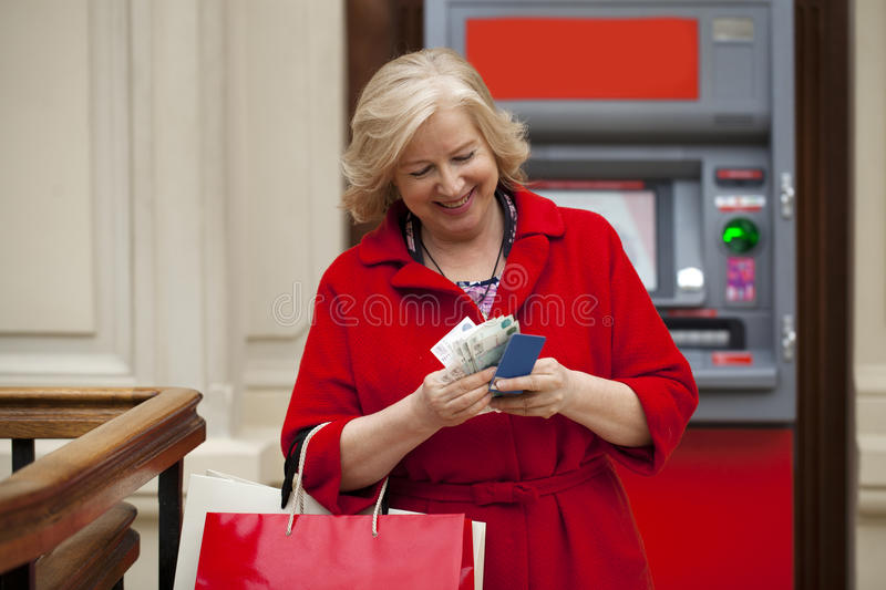 An elderly woman with shopping blonde is on the background in sh. Mature blonde woman with shopping bags on the background of the ATM stock image