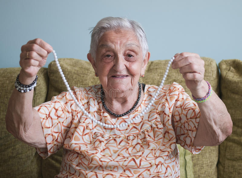 Elderly woman showing a necklace stock image