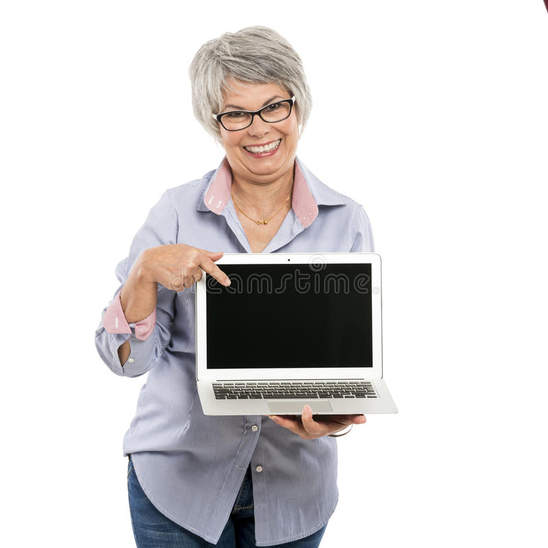 Elderly woman showing something on a laptop. Happy elderly woman holding and showing something on a laptop royalty free stock photo