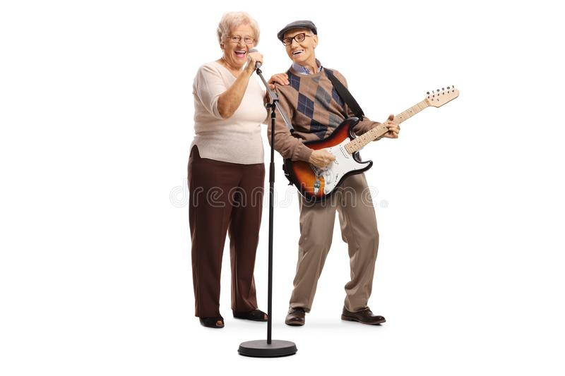Elderly woman singing on a microphone and an elderly gentleman playing a guitar. Full length portrait of an elderly women singing on a microphone and an elderly stock images