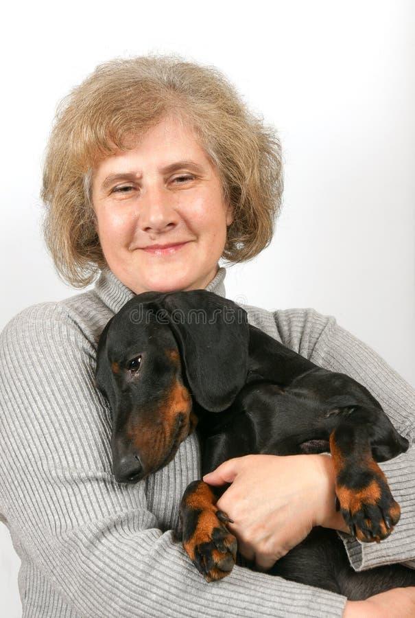 Elderly woman sits and embosom dachshund. Elderly smiling woman sits and embosom dachshund royalty free stock photo