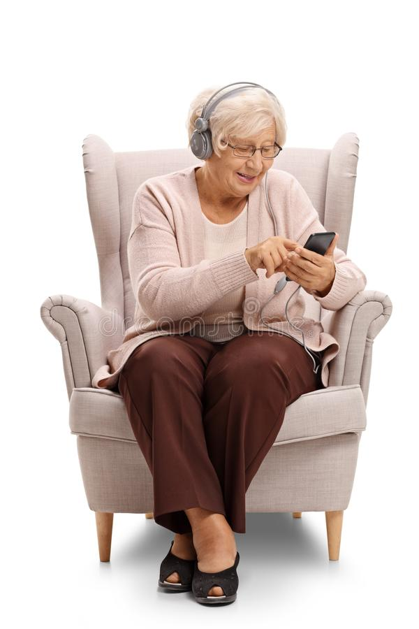 Elderly woman sitting in an armchair and listening to music on a stock images