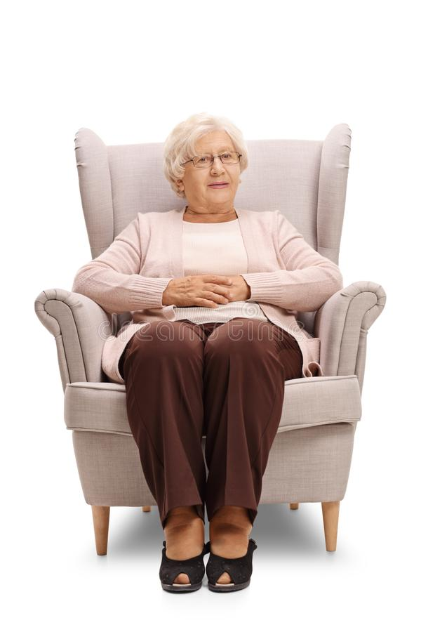 Elderly woman sitting in an armchair and looking at the camera royalty free stock photos
