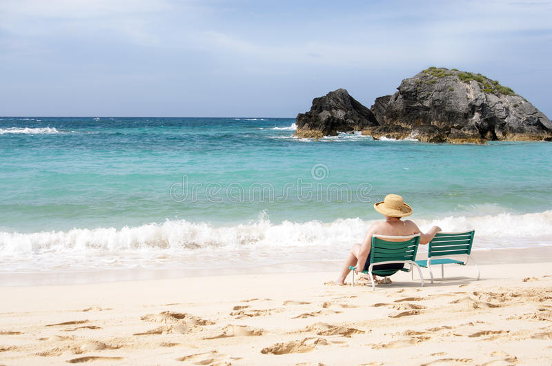 Elderly woman sitting at the beach royalty free stock photography