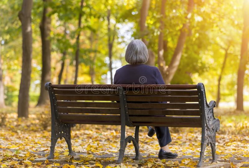Elderly woman sitting on a bench in autumn park royalty free stock photos