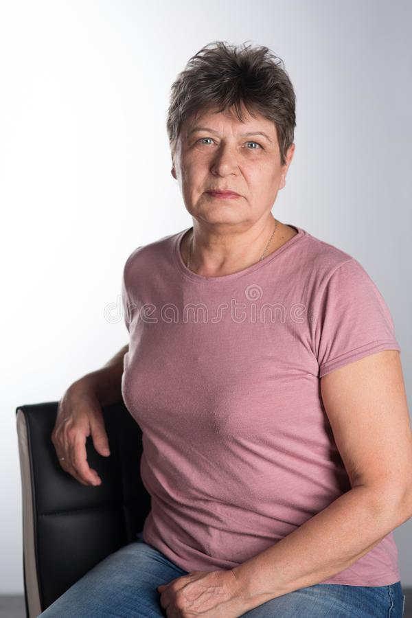 Elderly woman sitting on a chair stock photo