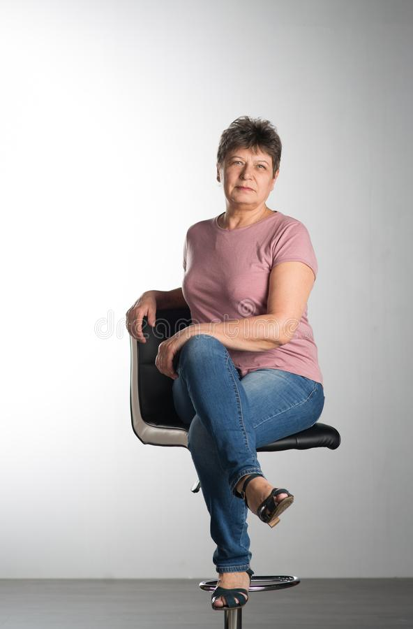 Elderly woman sitting on a chair stock image