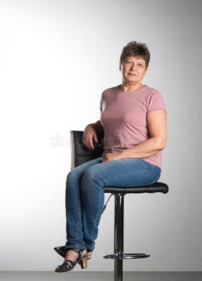 Elderly woman sitting on a chair stock images