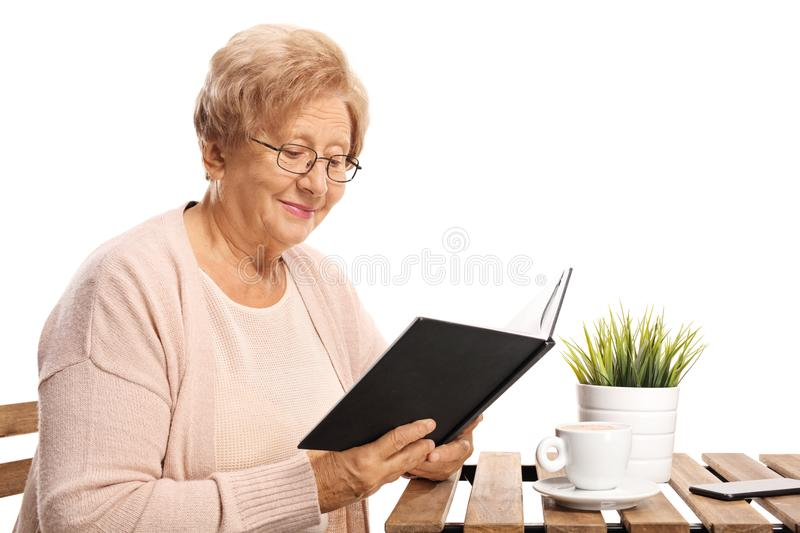 Elderly woman sitting at a coffee table and reading a book royalty free stock photography