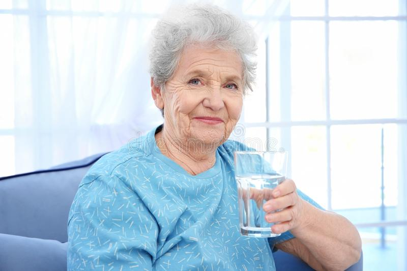 Elderly woman sitting on couch and holding glass of water. royalty free stock photography