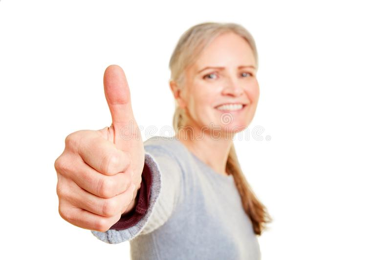 Senior woman holds thumbs up royalty free stock image