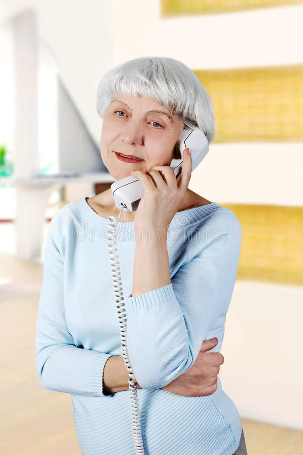 Elderly woman speaks on the phone royalty free stock photography