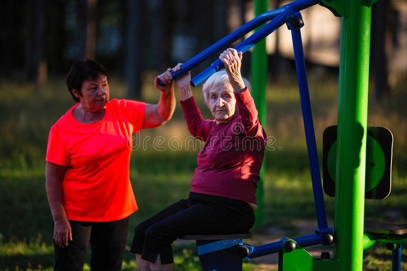 An elderly woman on the sport playground doing exercises on the simulator. royalty free stock photos