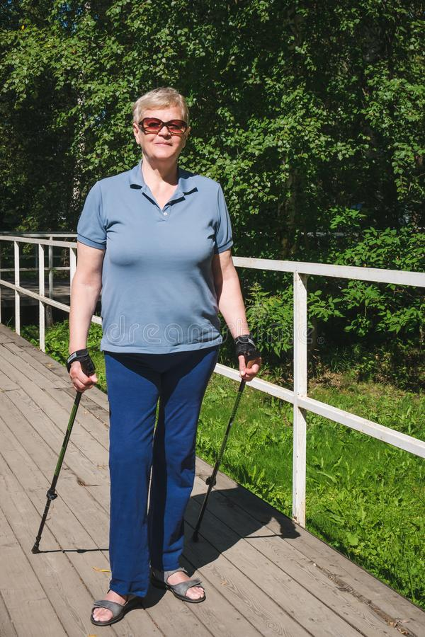 Elderly woman standing with Nordic walking poles in summer royalty free stock images