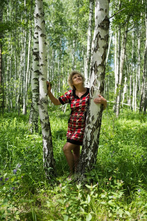Elderly woman stands at the birch and looks up. stock images