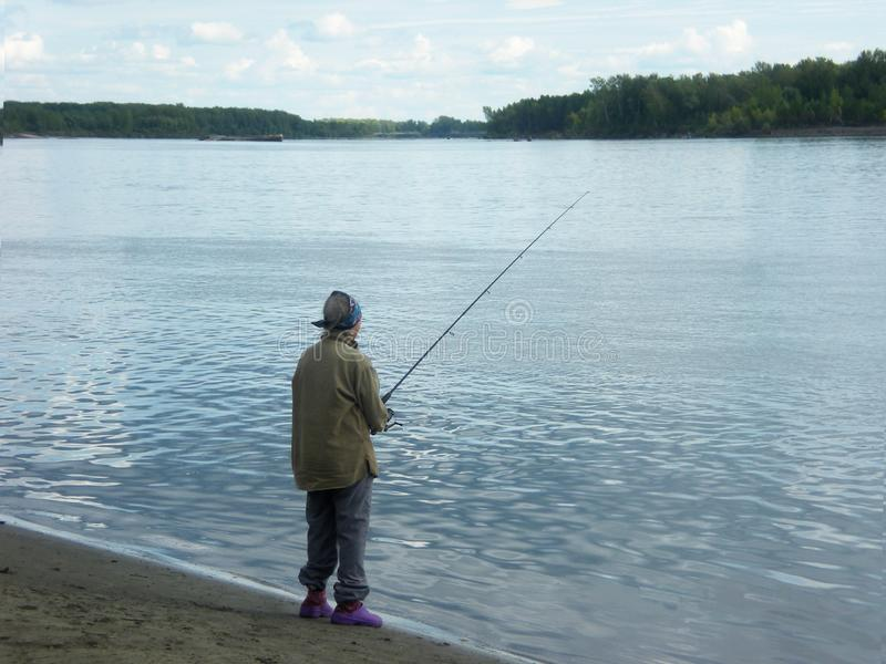An elderly woman stands with a spinning on the bank of the river, the concept of a healthy lifestyle, hobby of pensioners, stock image