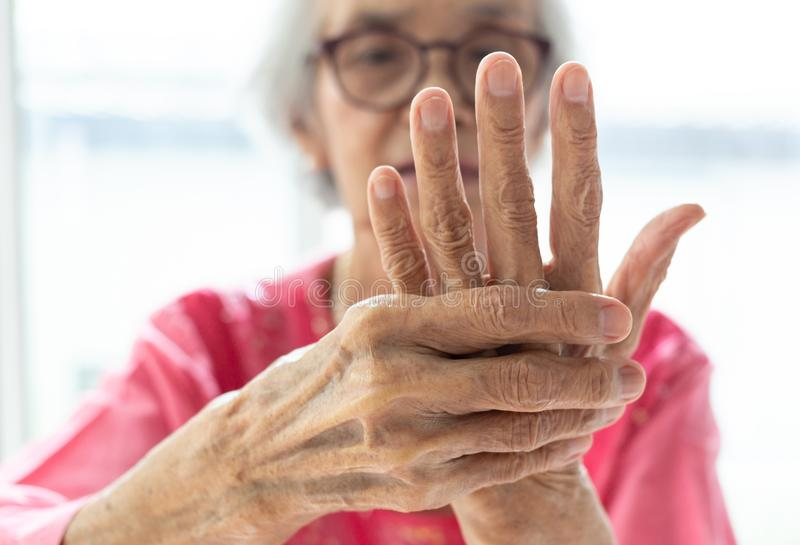 Elderly woman suffering from pain in hand royalty free stock photography