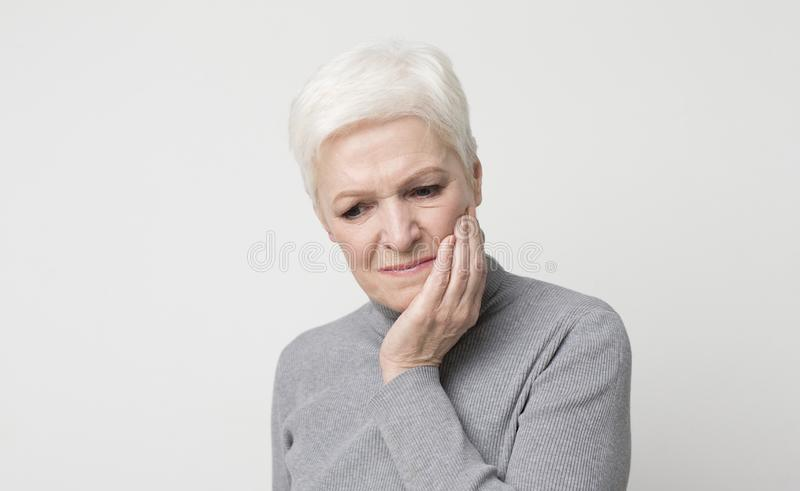 Elderly woman suffering from sudden tooth pain, panorama royalty free stock photography