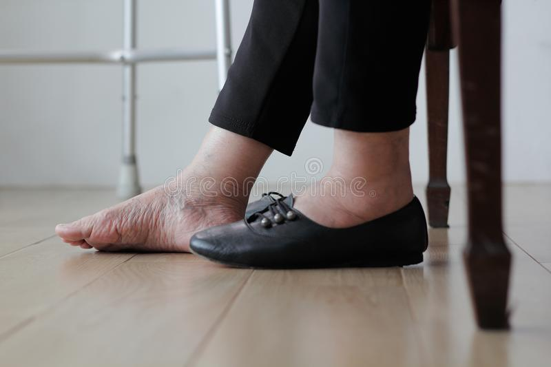 Elderly woman swollen feet putting on shoes. At home royalty free stock image