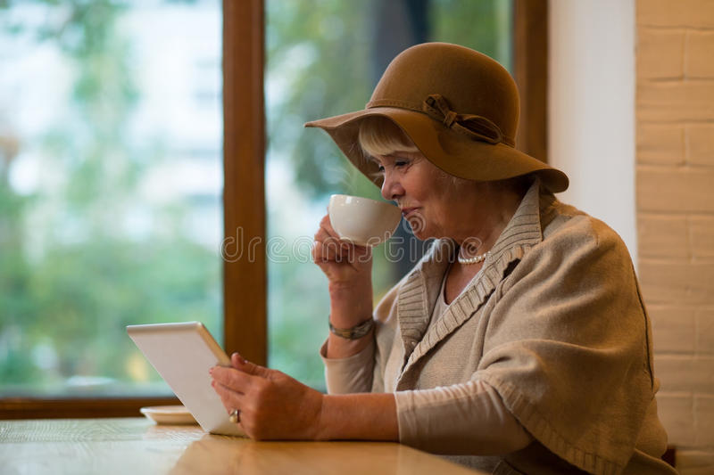 Elderly woman with tablet. Senior lady holding coffee cup. Create account in social network stock images