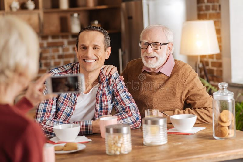 Elderly woman taking photo of her family at breakfast stock image