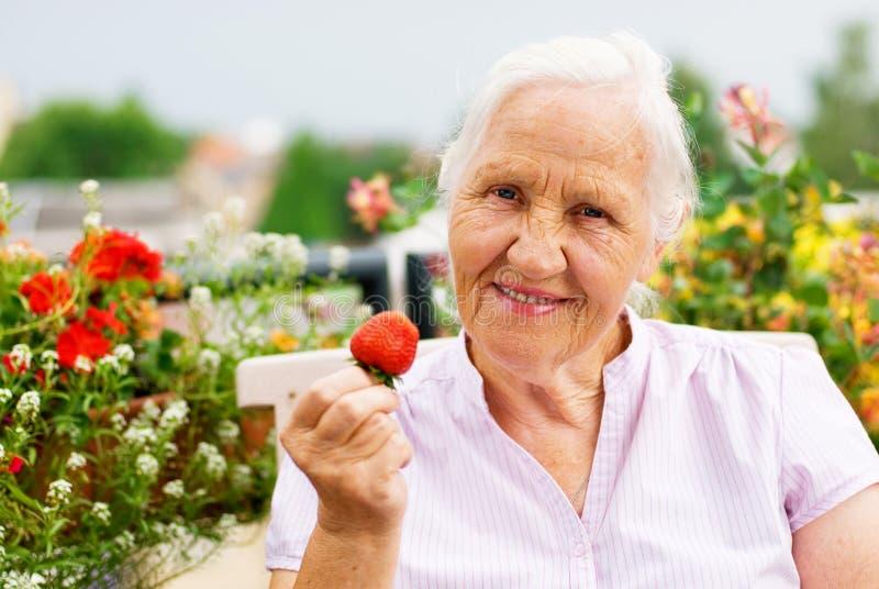 Elderly woman on the terrace. Elderly smiling woman sitting on the terrace, holding a strawberry stock photo