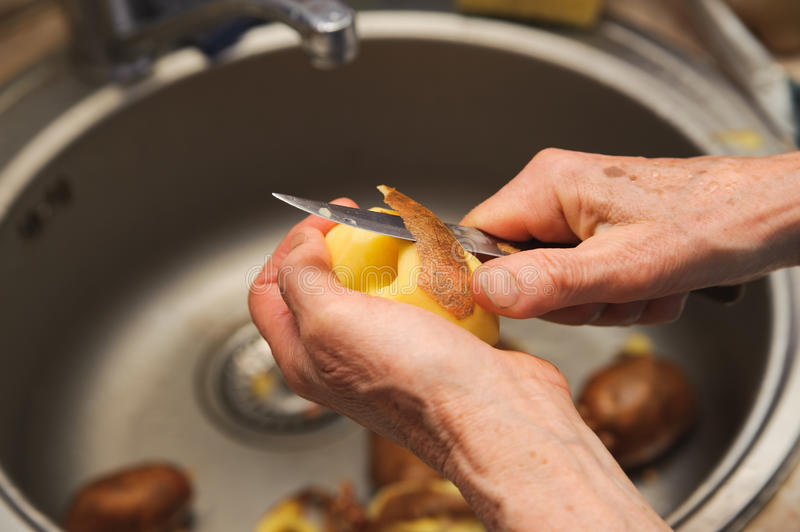 Elderly woman to peel potatoes. Kitchen working. Prepare food royalty free stock images