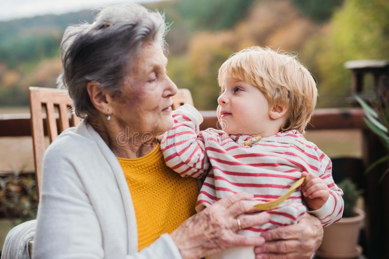 Elderly woman with a toddler great-grandchild on a terrace in autumn. royalty free stock photography