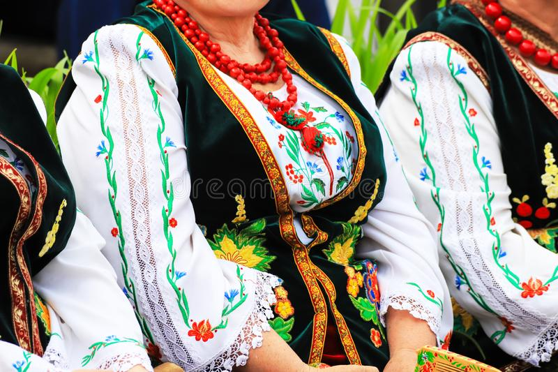 Elderly woman in traditional national  Ukrainian costume, embroidered blouse, embroidery, waistcoat and beads, detail, close-up. Ukraine royalty free stock image